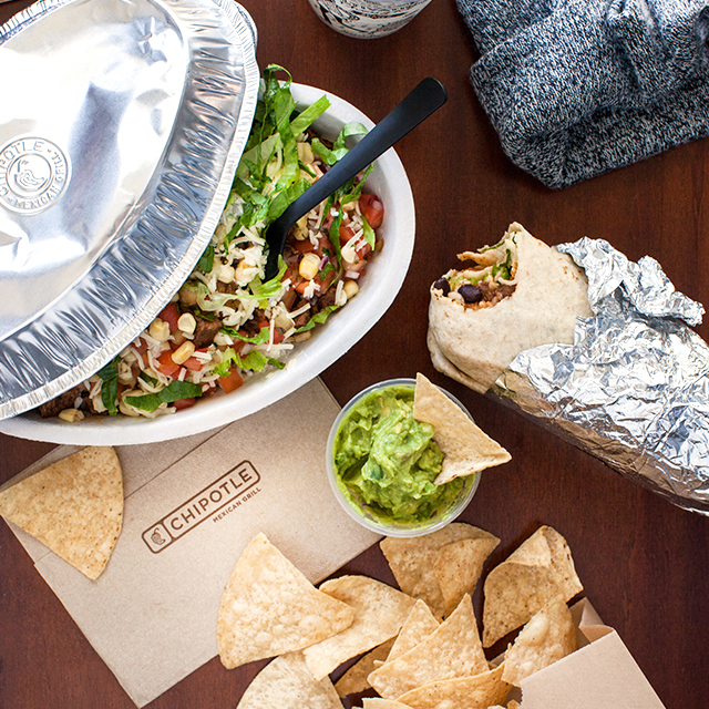 Image depicting a desk with a beanie hat, a chipotle bowl, burrito and guac and chips