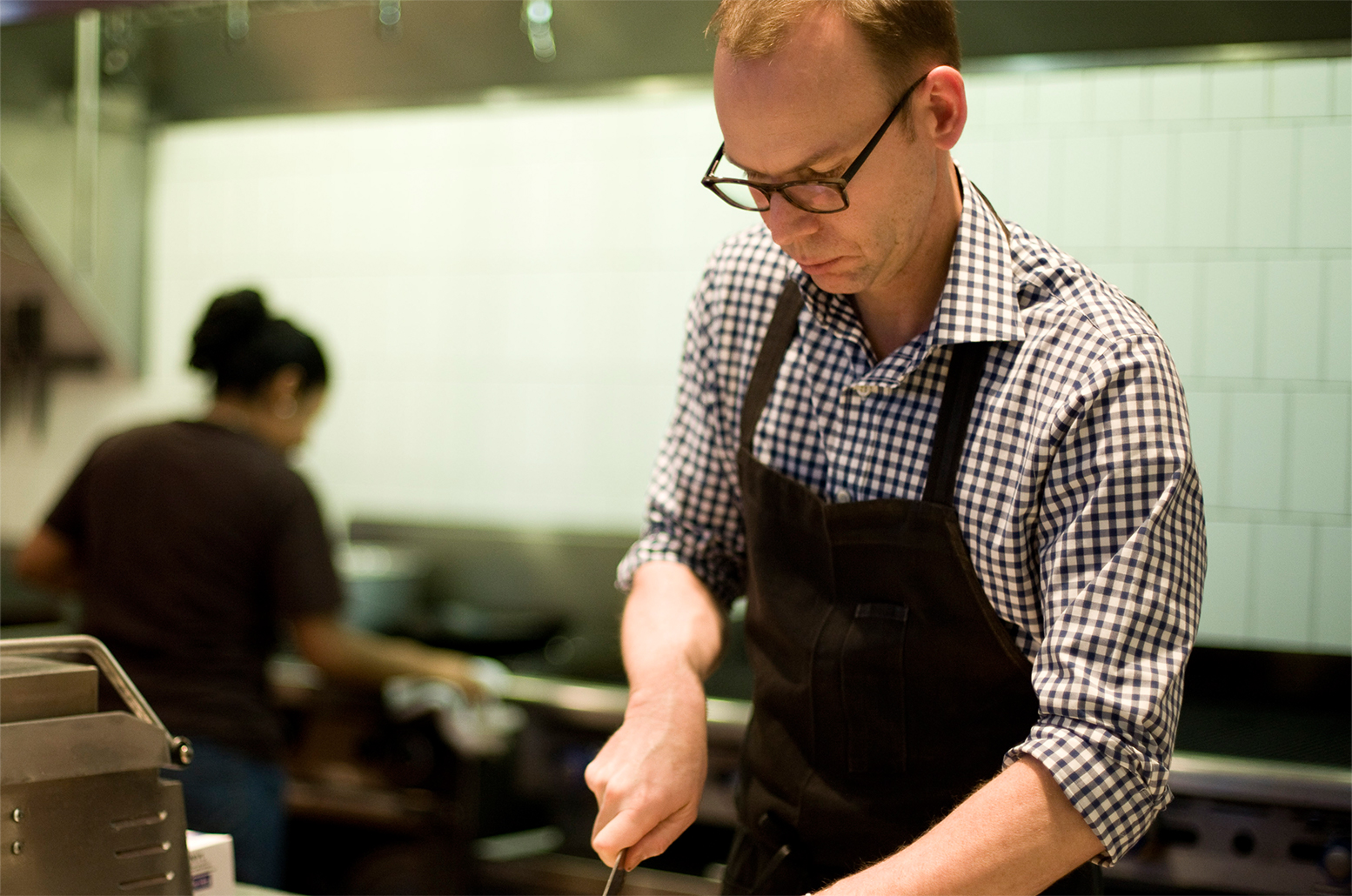 photo of founder and chairman steve ells chopping food in the kitchen